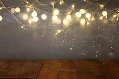 пустая таблица перед гирляндой золота рождества теплой освещает Стоковое Фото