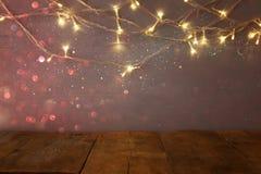 пустая таблица перед гирляндой золота рождества теплой освещает Стоковые Фотографии RF