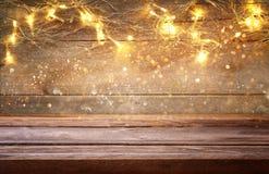 пустая таблица перед гирляндой золота рождества теплой освещает Стоковое Изображение