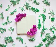Пустая тетрадь украсила пурпурные цветки на белой предпосылке, взгляде сверху Блокнот украшенный с зелеными листьями и фиолетом П иллюстрация вектора