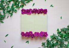 Пустая тетрадь украсила пурпурные цветки на белой предпосылке, взгляде сверху Блокнот украшенный с зелеными листьями и фиолетом r иллюстрация вектора