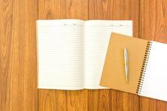 Пустая тетрадь с ручкой на деревянной предпосылке Стоковое фото RF