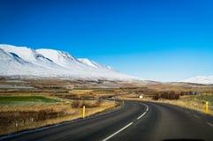 Пустая улица с исландским ландшафтом во время часа восхода солнца золотого Стоковые Фотографии RF