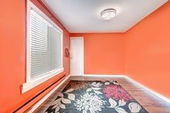 Пустая яркая красная комната с красочным половиком красный цвет дома входа двери стула нутряной самомоднейший Стоковые Фото