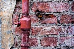 Пустите по трубам на предпосылке masonry кирпича в красном цвете, обрабатывать grunge стоковые фотографии rf
