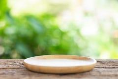 Пустое блюдо на деревянном столе с зеленой предпосылкой света нерезкости для стоковые изображения rf