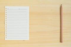 Пустое бумажное примечание с карандашем на деревянной предпосылке Стоковые Изображения