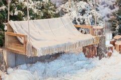 Пустое деревянное качание в покрытом снег парке или лесе с елевыми деревьями и пни, большие свечи в стеклянных вазах, пока Стоковые Фото