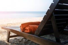 Пустое деревянное sunbed с оранжевыми полотенцами на пляже Стоковые Изображения RF