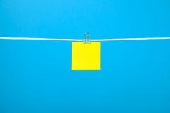Пустое желтое бумажное примечание на строке Стоковая Фотография