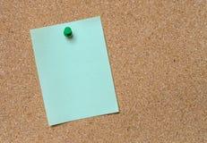 Пустое зеленое примечание прикалыванное на пробковой доске Стоковое Фото