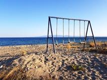 Пустое качание детей на дезертированном пляже Стоковые Фото
