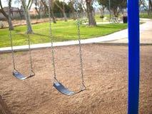 Пустое качание установило в парк с голубыми столбами Стоковая Фотография