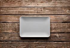 Пустое керамическое блюдо на старой таблице Стоковые Фотографии RF