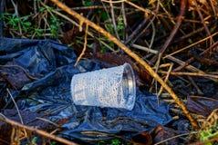 Пустое пластичное стекло лежит на черном пакостном пакете на открытом воздухе стоковые изображения rf