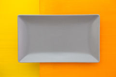 Пустое серое керамическое блюдо дальше над оранжевым и желтым деревянным столом Стоковое Изображение RF