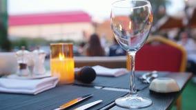 Пустое стеклянное положение на таблице - горя свече - outdoors ресторана акции видеоматериалы