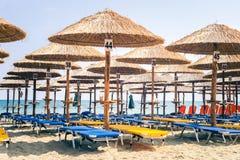 Пустое Sunchair Deckchairs на пляже под парасолями, обозревая t Стоковое фото RF