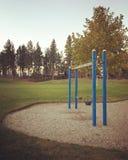Пустое swingset в поле с предпосылкой высоких деревьев Стоковая Фотография