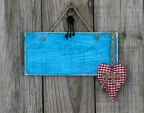 Пустой античный голубой знак с красными сердцем и утюгом пользуется ключом смертная казнь через повешение на затрапезной деревянн Стоковые Фото