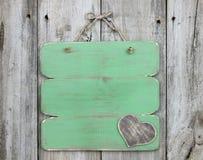 Пустой античный зеленый знак с деревянной смертной казнью через повешение сердца на старой выдержанной деревянной двери Стоковая Фотография