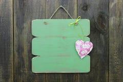 Пустой античный зеленый знак с флористической смертной казнью через повешение сердца на деревенской деревянной двери Стоковое Фото