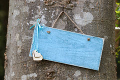 Пустой голубой знак при сердца вися на дереве в лесе Стоковая Фотография RF