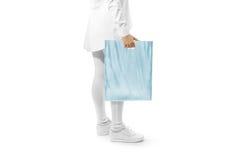 Пустой голубой модель-макет полиэтиленового пакета держа руку Стоковая Фотография