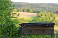 Пустой гриль BBQ портативной машинки перед свежим зеленым ландшафтом лета стоковая фотография rf