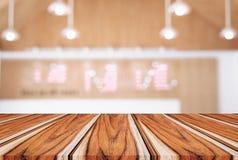 Пустой деревянный стол и запачканная предпосылка конспекта в переднем o Стоковое Изображение RF