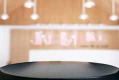 Пустой деревянный стол и запачканная предпосылка конспекта в переднем o Стоковое Фото