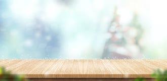 Пустой деревянный стол с абстрактными рождественской елкой нерезкости и снегом fa Стоковые Фото