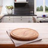 Пустой деревянный стол с доской пиццы и скатерть около окна в кухне Белый конец салфетки вверх по насмешке взгляд сверху вверх Ку стоковые фотографии rf