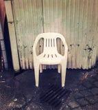 Пустой дешевый белый пластиковый стул в grungy проходе стоковое фото
