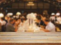 Пустой деревянный стол и запачканная dinning предпосылка людей Стоковое Изображение RF