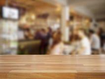 Пустой деревянный стол и запачканные люди в предпосылке кафа Стоковое фото RF