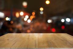 Пустой деревянный стол перед предпосылкой запачканной конспектом стоковое изображение