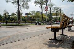 Пустой желтый стенд под деревом на пешеходе около улицы в центре города стоковое фото rf