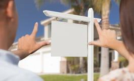 Пустой знак недвижимости, дом и руки воинских пар обрамляя Стоковые Фотографии RF