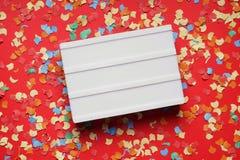 Пустой знак lightbox на красной бумажной предпосылке с confetti стоковые фотографии rf