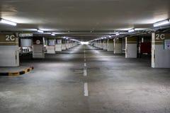 Пустой интерьер автостоянки космоса на после полудня Крытое место для стоянки интерьер гаража с автомобилем и вакантной парковки  стоковое изображение