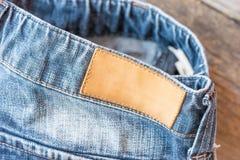 Пустой кожаный ярлык джинсов на голубые джинсы, деревянная предпосылка Стоковое Изображение RF