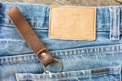 Пустой кожаный ярлык джинсов на голубые джинсы, деревянная предпосылка Стоковые Изображения RF
