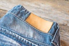 Пустой кожаный ярлык джинсов на голубые джинсы, деревянная предпосылка Стоковое Изображение