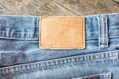 Пустой кожаный ярлык джинсов на голубые джинсы, деревянная предпосылка Стоковая Фотография RF