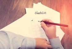 пустой контрольный списоок на листе бумаги деревянного стола a перед человеком с словами: Контрольный список Планирование дел на  Стоковая Фотография