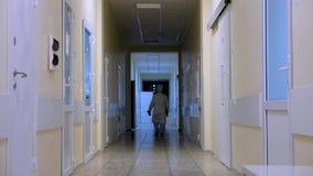 Пустой коридор клиники с доктором проходя мимо Частная клиника, больница, медицинский центр Медицинская реформа традиционного сток-видео