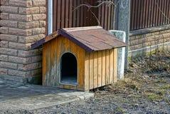 Пустой коричневый дом собаки около загородки Стоковые Фото