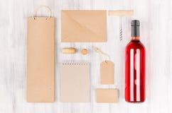 Пустой коричневый kraft упаковывая, канцелярские принадлежности, товар установил с розовым вином бутылки на мягкой белой деревянн стоковое фото