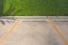Пустой космос места для стоянки автомобиля с зеленым кустом на заднем плане на общественном парке Стоковая Фотография RF